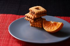 Chocolate chip cookies and piece of orange on plate and on red and black background with place for text selective focus with copys. Chocolate chip cookies and Stock Photography