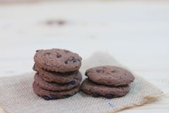 Chocolate chip cookies are placed on sackcloth on a wooden table stock photo