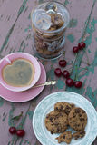 Chocolate Chip Cookies, Sour Cherries and Coffee. Chocolate Chip Cookies on a Plate, a Glass Cookie Jar, Sour Cherries and a Cup of Black Coffee on a Vinatge Stock Images