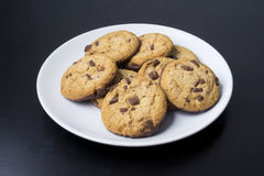 Chocolate chip cookies on a white plate. On a dark background Royalty Free Stock Image