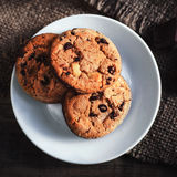 Chocolate chip cookies on white plate dark old wooden table with Stock Photo