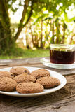 Chocolate chip cookies on white plate with a glass of coffee. Royalty Free Stock Photography