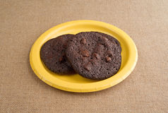 Chocolate chip crispy brownie cookies on yellow plate Stock Image