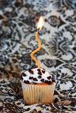 Chocolate chip cupcake with orange candle royalty free stock images
