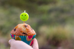 Chocolate chip cupcake and smiley candle. Royalty Free Stock Photo