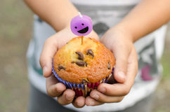 Chocolate chip cupcake and smiley candle. Stock Photography
