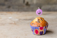Chocolate chip cupcake and smiley candle. Royalty Free Stock Image
