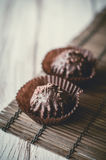 Chocolate chip muffin in brown wax paper. Unwrapped. Cocoa powder in the background Stock Photos