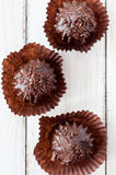 Chocolate chip muffin in brown wax paper. Unwrapped. Cocoa powder in the background Stock Photo