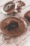 Chocolate chip muffin in brown wax paper. Unwrapped. Cocoa powder in the background Royalty Free Stock Images