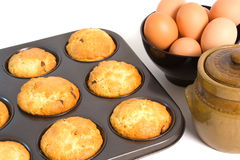 Chocolate Chip Muffins. Freshly baked Chocolate Chip Muffins in baking tray with eggs over white background Royalty Free Stock Photos