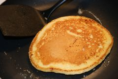 Chocolate chip pancake cooking on stove top frying pan. A chocolate chip pancake is cooking in this pan. Pancakes are a traditional canadian and western culture Royalty Free Stock Images