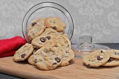 Chocolate chip cookies spilling out of a glass cookie jar. Stock Photography