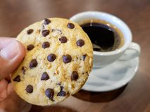 Chocolate chips cookie hand pickd to mouth with a cup of black coffee stock photo