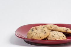 Chocolate chips cookies. On a red plate ready to serve royalty free stock image