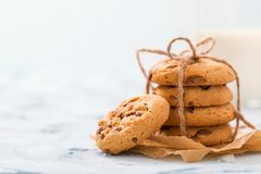 Chocolate chips cookies tied in stack on craft baking paper and glass of milk on pastel blue background stock photos