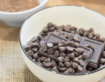Chocolate chips and Dark chocolate bar in white bowl. Stock Image