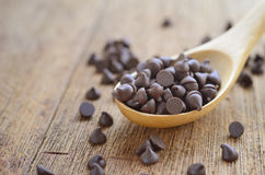 Chocolate chips. Focus at chocolate chips on wood table Stock Images