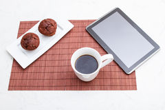 Chocolate chips Muffins with a cup of coffee and a tablet PC Stock Image