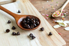 Chocolate chips on wooden spoon and ingredients for cooking Stock Photography