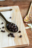 Chocolate chips on wooden spoon and ingredients for cooking Royalty Free Stock Images