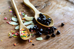 Chocolate chips on wooden spoon and ingredients for cooking Royalty Free Stock Photography