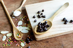 Chocolate chips on wooden spoon and ingredients for cooking Royalty Free Stock Image