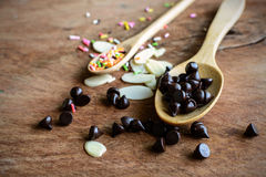 Chocolate chips on wooden spoon and ingredients for cooking Royalty Free Stock Photos
