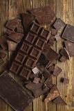 Chocolate chocolate chunks. Chocolate bar pieces. large bar of chocolate on wooden background. Chocolate candies. Background wit Royalty Free Stock Photography