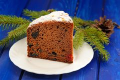 Chocolate christmas fruit cake, fur brunch and cone on blue tabl Stock Photo