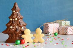 Chocolate Christmas tree and gingerbread men on blue background. Happy New Year and Merry Christmas concept. Copy space.  stock photo