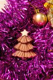 A chocolate christmas tree shape displayed with tinsel and golden Christmas decorations Stock Photo