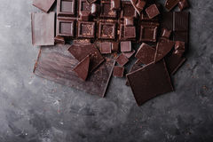 Chocolate chunks. Chocolate bar pieces. A large bar of chocolate on gray abstract background. C Royalty Free Stock Image