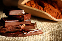 Chocolate chunks. Close up of dark chocolate in pieces with cocoa on a wooden spoon Royalty Free Stock Photos