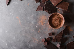 Chocolate  chunks and cocoa powder. Chocolate bar pieces.  A large bar of chocolate on gray abstract background. Stock Photos