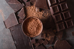 Chocolate chunks and cocoa powder. Chocolate bar pieces. A large bar of chocolate on gray abstract background. royalty free stock images