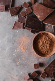 Chocolate chunks and cocoa powder. Chocolate bar pieces. A large bar of chocolate on gray abstract background. Stock Photography