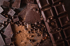 Chocolate  chunks and cocoa powder. Coffee beans Chocolate bar pieces. Large bar of chocolate on gray abstract background. Royalty Free Stock Photography