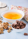 Chocolate chunks, eggs, butter, nuts and cup of flour Stock Photos