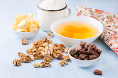 Chocolate chunks, eggs, butter, nuts and cup of flour Stock Photo