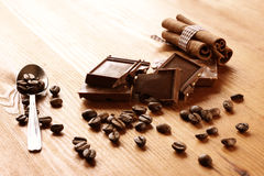 Chocolate, cinnamon and coffee beans on wooden table. selective focus. natural light. Royalty Free Stock Photos