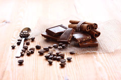 Chocolate, cinnamon and coffee beans on wooden table. selective focus. natural light. Stock Photos