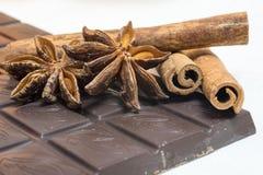 Chocolate, cinnamon sticks and star anise. Tender milk chocolate and cinnamon with anise on a wooden background Stock Image