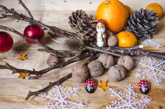 Chocolate, citrus fruits,nuts with cones and toys on boards Royalty Free Stock Photos