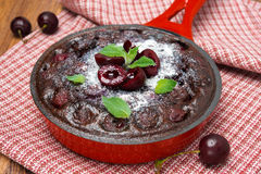 Chocolate clafoutis with cherries in a frying pan, close-up Stock Photo