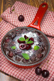 Chocolate clafoutis with cherries in a frying pan, top view Royalty Free Stock Photos