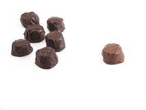 Chocolate clique. One milk chocolate exiled from clique of dark chocolates stock photos