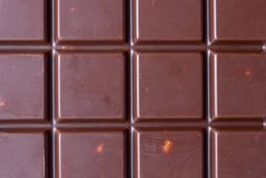 Chocolate closeup background. Cell chocolate bars with almonds. Chocolate brown Stock Image
