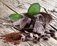 Chocolate and cocoa bean over wooden background. Royalty Free Stock Images