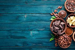 Chocolate, cocoa and cocoa beans on a blue wooden background. Top view.